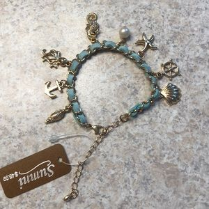Gold bracelet with teal color leather material.
